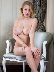 Busty blonde babe absolutely naked spreading legs on the chair